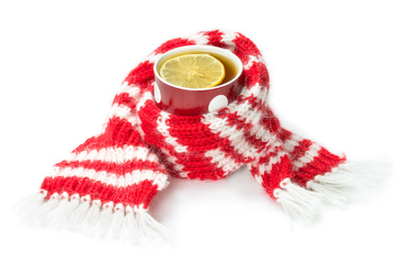 Red wool scarf, wrapped around a cup of tea, isolated on a white  photo