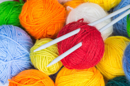 Colorful balls of wool yarn and knitting needles photo