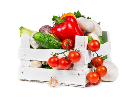 Fresh vegetables in a painted wooden box isolated on white background photo