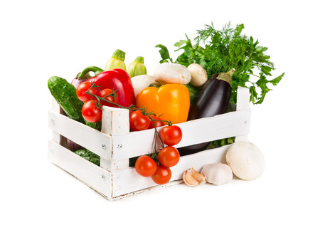 produce: Fresh vegetables in a painted wooden box isolated on white background