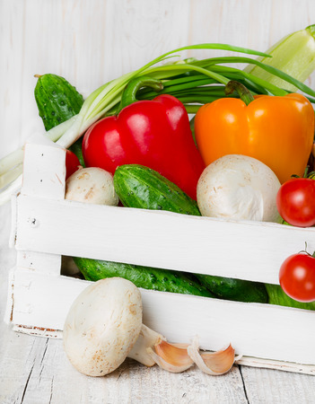 Fresh vegetables in a wooden box white color photo