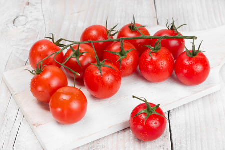 Cherry tomatoes on a white board photo