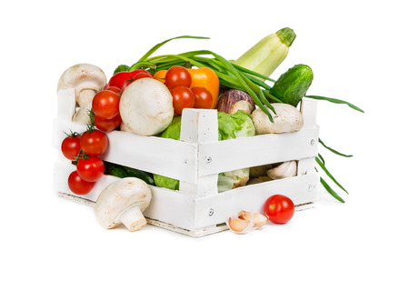 Fresh vegetables in a wooden box isolated on white background photo