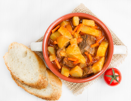 Stewed potatoes with meat, carrots and tomatoes photo
