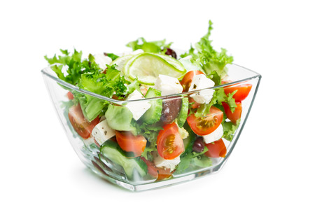 Salad with fresh vegetables in a glass bowl isolated on white background Stock Photo