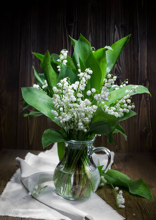 Lilies of the valley in a glass jug on the wooden  photo