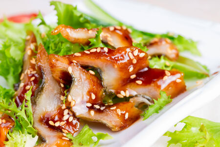 Salad with smoked eel in the unagi sauce and sesame seeds. photo