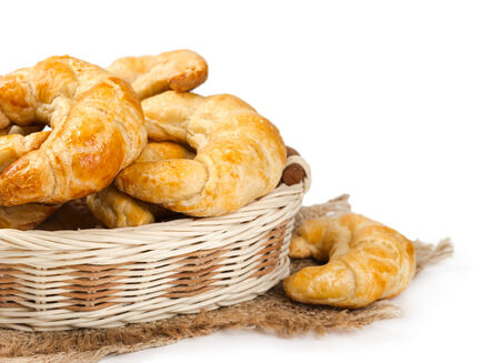 Croissants in a wicker basket isolated on white background photo
