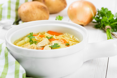 Soup with noodles and chicken in a white ceramic bowl photo