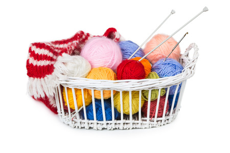 Wicker basket with colorful balls of yarn isolated on white background photo