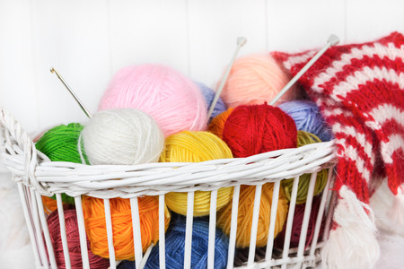 Wicker basket with colorful balls of knitting photo