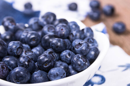 Blueberries in a white ceramic bowl on jeans fabric photo