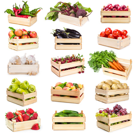Set of wooden boxes with vegetables, fruits and berries isolated on white background photo