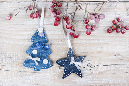 Christmas trees and stars on a branch with berries on wooden background photo
