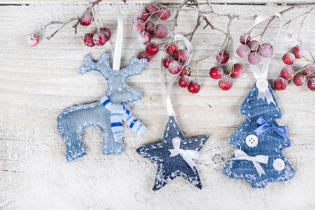 Christmas tree, reindeer and star on a branch with berries on wooden background photo