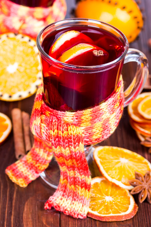 Hot mulled wine with orange slices and cinnamon sticks. photo