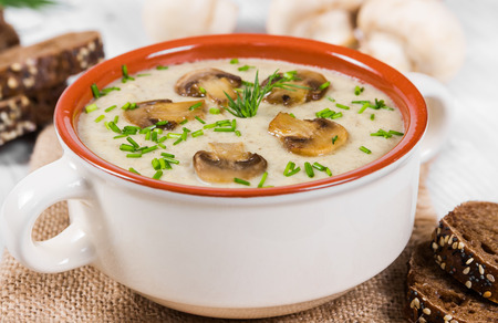 Cream soup with mushrooms on a wooden background photo