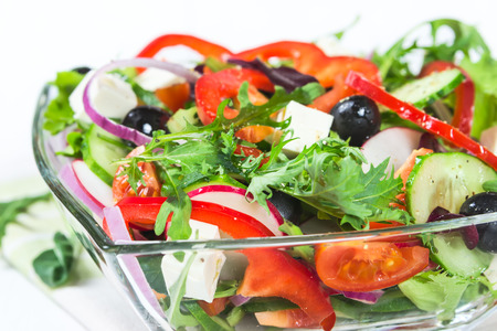 Salad with fresh vegetables and herbs in a glass bowl