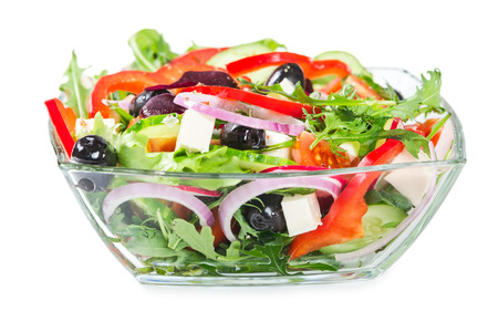Salad with fresh vegetables, olives and cheese in a glass bowl isolated on white background
