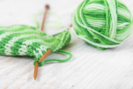 skein: Knitting pattern of green yarn on wooden needles and skein on a wooden background