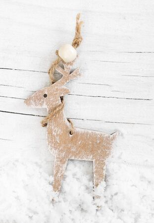 wooden reindeer: Decorative wooden reindeer on snowy white background Stock Photo