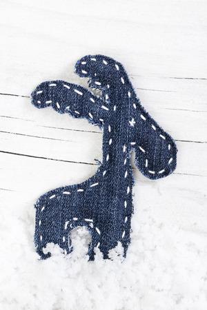 reno: Decorativo renos de Navidad en la nieve sobre fondo de madera