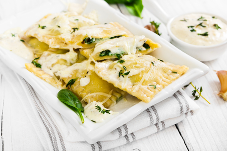 fresh spinach: Ravioli with spinach and ricotta cheese with white sauce and grated Parmesan