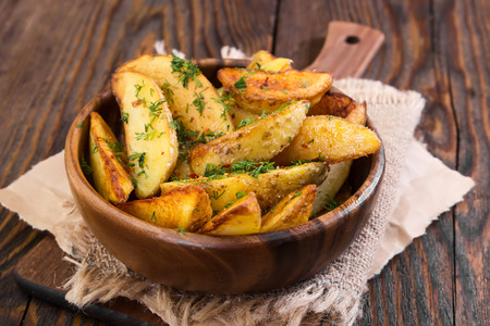 Potato country style with dill in wooden bowl on wooden background