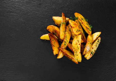 Potato wedges on black background. Top view. Stock Photo