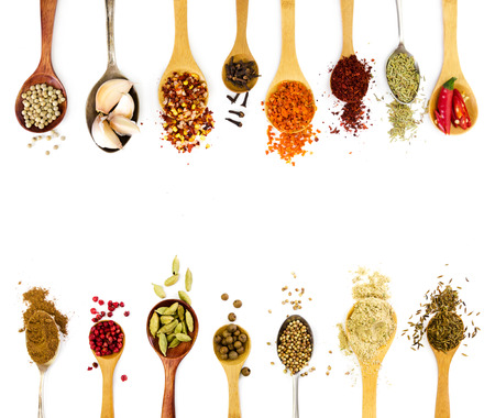 green herbs: Spices in spoons isolated on white background. Top view.