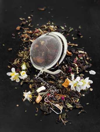 tea strainer: Herbal fragrant tea with flowers in tea strainer on black rustic background Stock Photo