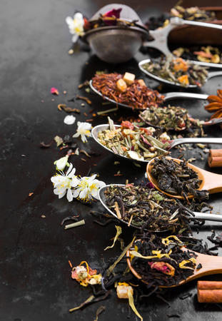 Aromatic flower tea in spoon on rustic black background. Stock Photo