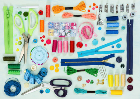 Sewing tool and accessories on painted background blue color, top view. Flat lay.