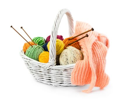 basket embroidery: Balls of woolen threads for knitting in wicker basket isolated on white background.