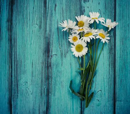 Bouquet de camomilles sur bleu vintage fond en bois. à plat. Vue de dessus.