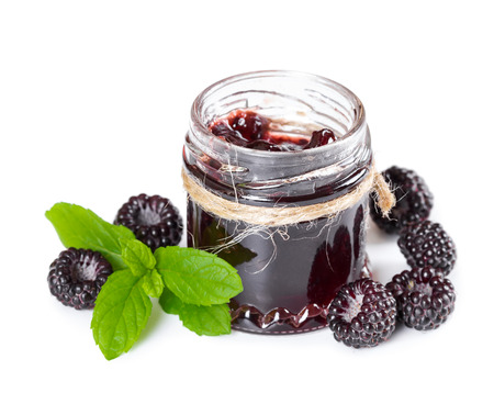 black raspberries: Jam made from black raspberries Cumberland in glass jar and leaves of mint isolated on white background Stock Photo
