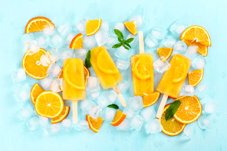Fruit homemade popsicle with slices of orange and ice cubes on light blue background. Top view.
