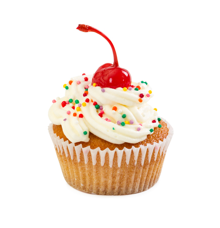 Muffin with cream and maraschino cherry, decorated with colorful candy sprinkles, isolated on white background