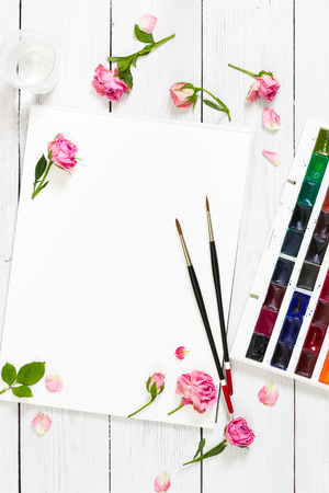 flat brushes: Flat lay composition with sketchbooks, brushes, watercolor paints and pink roses on light wooden background. Top view.