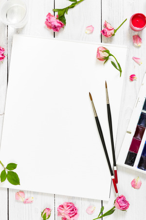 flat brushes: Workplace of artist. Paper, brushes, watercolor paints, palette and pink roses. Flat lay composition. Top view. Stock Photo