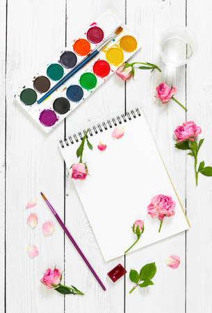 flat brushes: Workplace of artist. Sketchbooks, brushes, watercolor paints and pink roses. Flat lay composition. Top view. Stock Photo