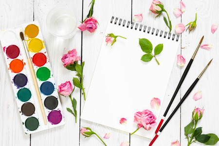 flat brushes: Workplace of artist. Paper, brushes, watercolor paints and pink roses. Flat lay composition. Top view.