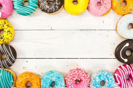 Colorful donuts on light wooden background and space for text. Top view. Фото со стока