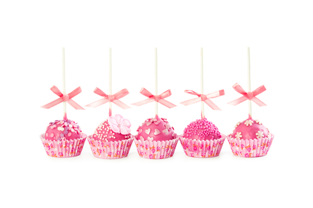 Five romantic pop cake with pink frosting, decorative sprinkles and pink ribbons isolated on white background.
