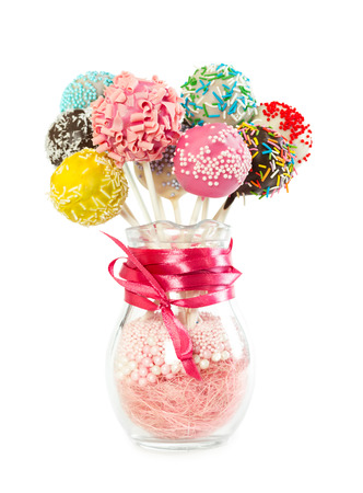 Colorfull cake pops with decorative sprinkles in glass vase isolated on white background Stock Photo