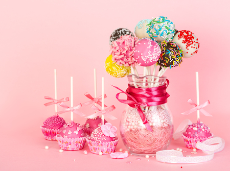 Cake pops with pink icing and decoration on paper form and colorful cake pops in glass vase on pink background