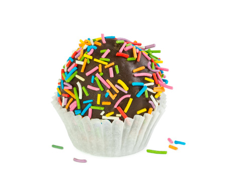 Chocolate cake ball with colorful sprinkles in paper form isolated on white background Stock Photo