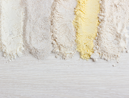 Different types of flour on wooden table, top view
