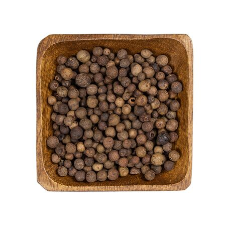 Allspice in wooden bowl isolated on white background. Top view. Standard-Bild