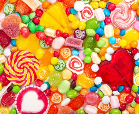 Colorful lollipops and different colored round candy. Top view. Imagens
